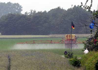 Bauer spritzt Pestizide neben Deutschlandfahne